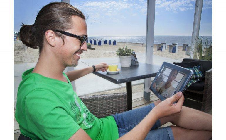 strandtent kijkend naar tablet